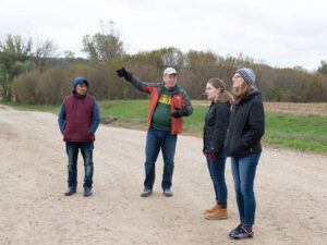 Photo of Dr. Carter Smith talking with students in his community-based Spanish language class during a visit to a nearby farm that employs migrant workers.