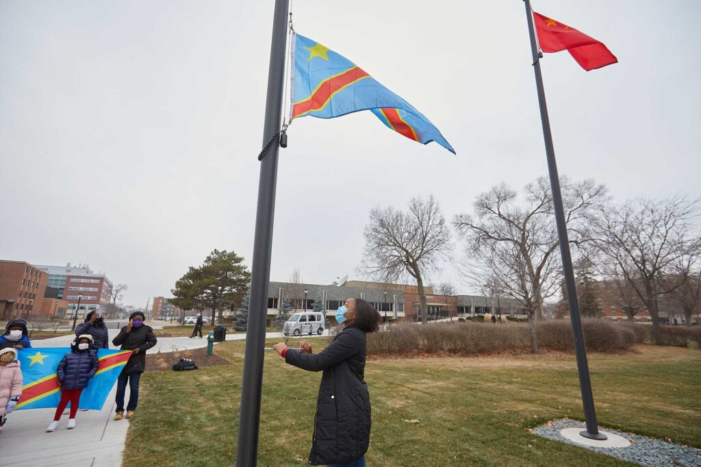"Photo of UWL Senior Vanessa Mbuyi Kaja raising the flag of the Democratic Republic of Congo for the first time on campus during a December 2020 ceremony. ""I already knew I was accepted here in La Crosse, but this makes me feel like yes, I can call this my home,"" noted the microbiology major."