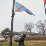 """Photo of UWL Senior Vanessa Mbuyi Kaja raising the flag of the Democratic Republic of Congo for the first time on campus during a December 2020 ceremony. """"I already knew I was accepted here in La Crosse, but this makes me feel like yes, I can call this my home,"""" noted the microbiology major."""