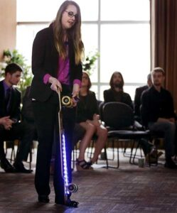 Photo of Kristen Holtan demonstrating a longboard outfitted with LED lights during the CEO elevator pitch competition finals on Wednesday, Oct, 12, 2016, at Whitewater University Innovation Center, in which she won first place.