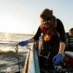 Photo of students collecting data and water samples from Lake Mendota during an early morning outing in 2016 for a limnology experiment. Limnology researchers discovered the spiny water flea in Lake Mendota in 2009. PHOTO: JEFF MILLER
