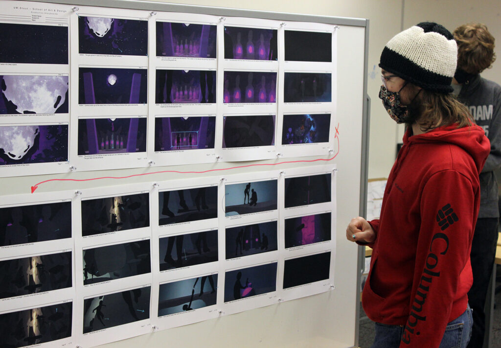 Photo of student Jonah Hammen studying a storyboard in the Animation Production class. / UW-Stout photo