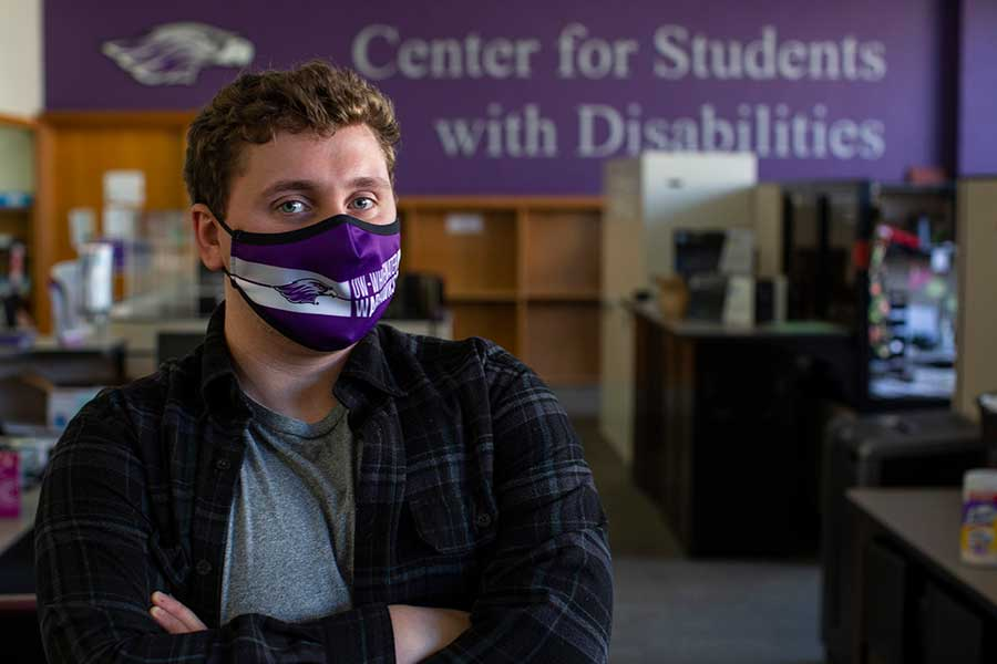 """Photo of Thomas """"TC"""" Hamilton, a psychology major, in the office of the Center for Students with Disabilities, where he is a student worker. TC started a scholarship for students with disabilities, Warhawk Inspired, that includes donations from other CSD staff and will first be awarded in fall 2021."""