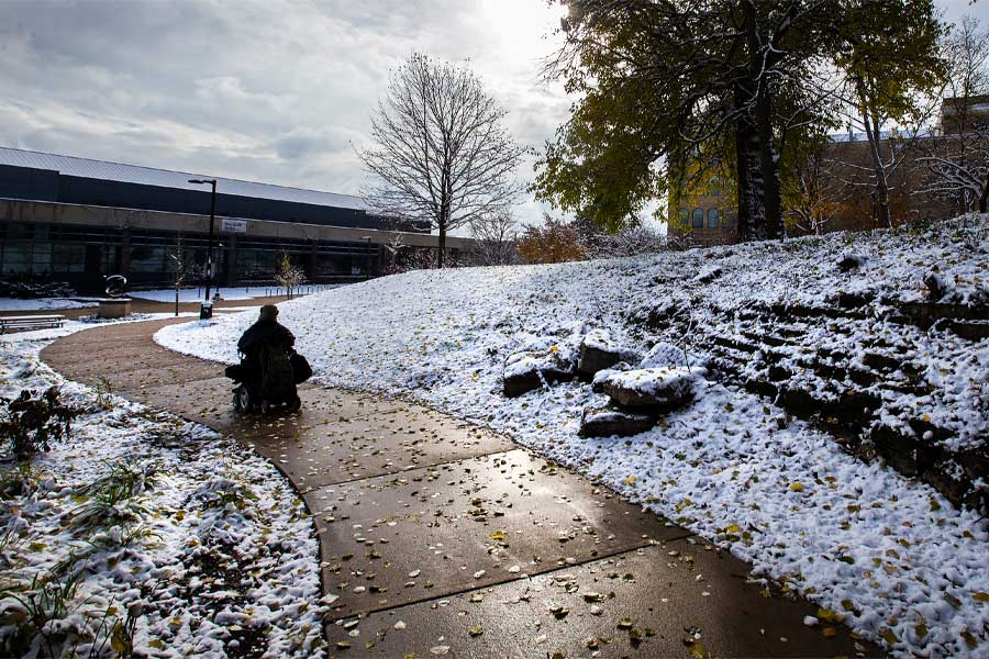 Photo of Kevin Kollmann, a chemistry major from Fond du Lac, who traveled along a sunlit sidewalk after an early season snowstorm blanketed the UW-Whitewater campus.