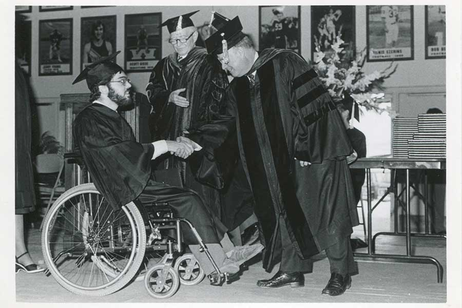 Photo of Chancellor James R. Connor, right, congratulating a student at commencement.