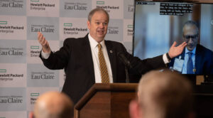 Photo of UW-Eau Claire Chancellor James Schmidt talking about a new public-private collaboration between Hewlett Packard Enterprise and the university at a Monday press conference. Pictured in the video screen is Mayo Clinic Health System Dr. Rajeev Chaudhry.