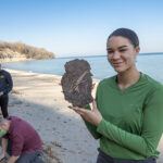 Photo of UWM student Mikayla Walker showing a fragment of peat with well-preserved plant and insect material unearthed at Sheridan Park in Cudahy. The fossil was found at the bottom of a bluff containing sedimentary strata deposited under a nearly mile-thick glacial at the end of the last ice age. Behind Walker are student Rene Chavez and geosciences lecturer Scott Schaefer. (UWM Photo/Troye Fox)