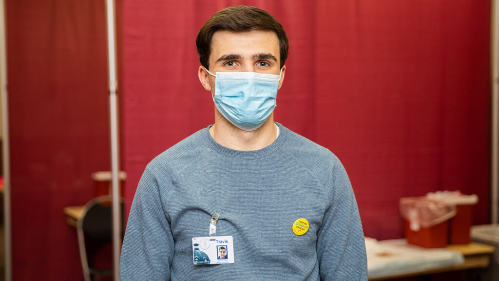 Photo of Travis Clary, who is interning at the Grant County Health Department, assisting at the vaccination clinics on campus.
