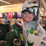 Photo of Alumni Director Kari Moody loads-up on Phoenix pride items from The Phoenix Bookstore.