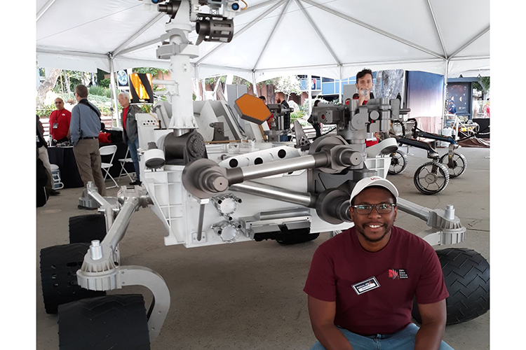 Photo of Darian Dixon posing in front of a model of the Curiosity rover, which landed on Mars in 2012. (Photo courtesy of Darian Dixon)