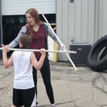 Photo of Kinesiology senior Brianna Roberts as an intern at Sports AdvantEdge in Verona working with young athletes.