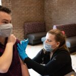 Photo of UW-Stevens Point student Nicholas Tierman receiving his COVID-19 vaccine from Hanna Christensen, one of several UWSP nursing students who are assisting with COVID-19 care and vaccination this spring.