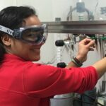 Photo of Jordan Munos, who as a member of the student research team in the chemistry lab with Dr. James Phillips, found her passion for biomedical research. She is pictured here installing a liquid nitrogen trap on the preparatory vacuum line, just one of many complex instruments Blugold researchers like Munos learn to master.