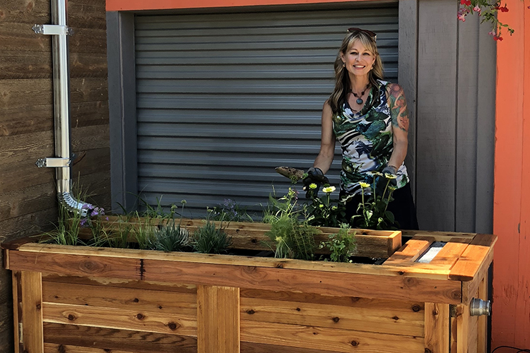 Photo of Carrie Bristoll-Groll showing off StormGUARDen, a product her company launched that serves as a combination rain garden and rain barrel. (Photo courtesy of Carrie Bristoll-Groll)