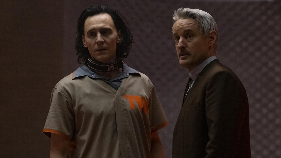 Photo of scene from new Marvel series, Loki, featuring actor Owen Wilson (right) playing Mobius, made to physically resemble UW Oshkosh alum Mark Gruenwald, who had a storied career with Marvel Comics until his unexpected death in 1996.