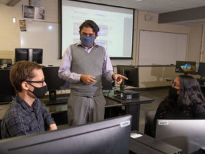Photo of Dr. Rahul Gomes (center), an assistant professor of computer science at UW-Eau Claire, talking with his student researchers Aaron Huber (left) and Avi Devy Mohan (right) about a collaborative project they are working on with Mayo Clinic Health System.