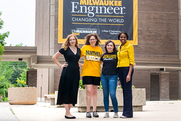 Photo of Bryn Glennon (left) and Mara Charpentier (third from left), who are two of the first three UWM graduates from the PECS program, which aims to boost the number of students from underrepresented groups who become engineers and computer scientists. With them are Wilkistar Otieno (right), associate professor of engineering, and Christine Beimborn, STEM outreach specialist in engineering. (UWM Photo/Elora Hennessey)