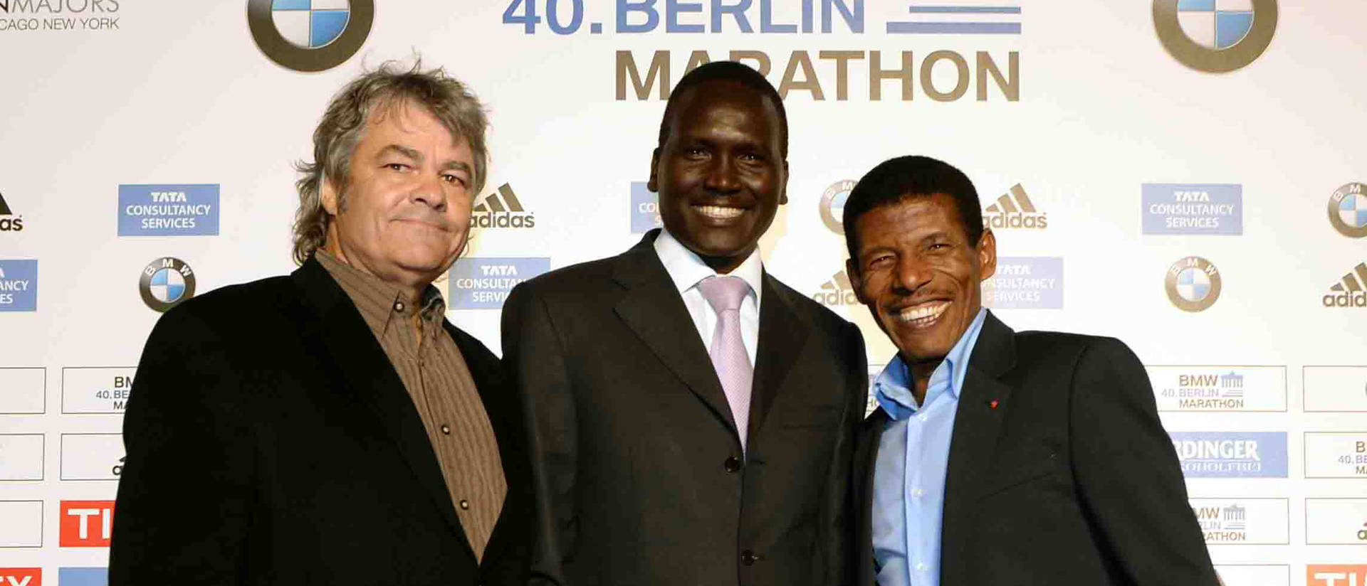 Photo of Dr. Sean Hartnett, UW-Eau Claire professor of geography, standing with marathoners Paul Tergat, center, and Haile Gebrselassie at a 2011 celebration of world record holders at the 2011 Berlin Marathon.