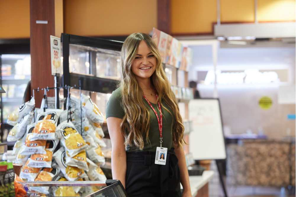 """Photo of Paige Ford inside a Kwik Trip. Kwik Trip has tens of thousands of enthusiastic fans, including Brent Erdmann of New London, who visited 615 unique Kwik Trip locations in 2020. """"The love we get from our followers is just crazy,"""" Forde says."""