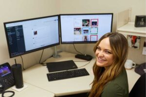 Photo of UWL graduate Paige Ford in front of computer screens. By giving Kwik Trip's social media accounts a new and engaging voice, Forde has helped grow the company's following on Facebook (600,000 likes), Instagram (88,000 followers), TikTok (76,000 followers) and Twitter (67,000 followers).