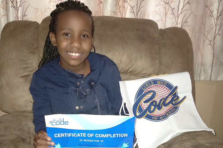 Photo of Elsie Maingi at her home in Nairobi, Kenya. Elsie shows off the certificate and tote bag she received from the Girls Who Code program at UWM. (Photo courtesy of Lilian Wangechi)