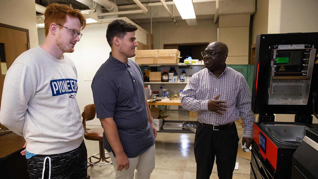 Photo of Dr. John Obielodan explaining the workings of a newly acquired selective laser sintering machine to some of his students in the lab. The machine was purchased through a Dairy Innovation Hub Supplies and Equipment grant.
