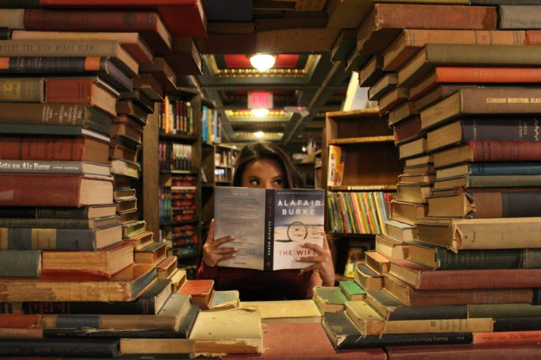woman in the middle of stack of books