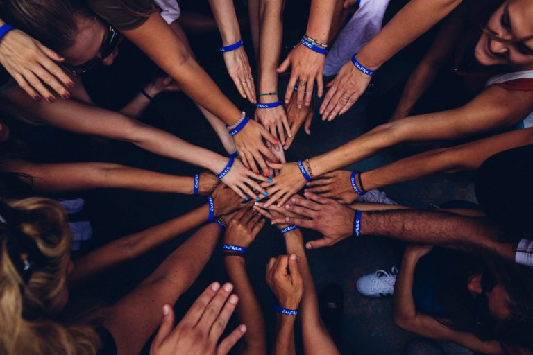 Several hands joined in a circle