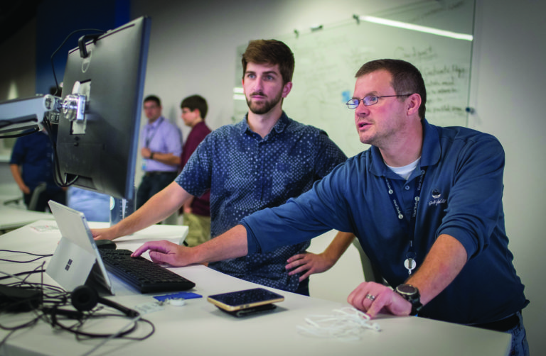 Photo of Matt Kleine (left), who was among the first to begin working at the Sentry IT Co-op with manager Steve Fox. A December graduate of UW-Stevens Point, Matt is now a full-time associate with Sentry Insurance. (UW-Stevens Point photo)