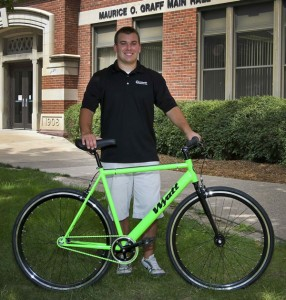 business owner posing with his single-speed bike