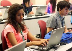 students work on their writing skills at a laptop station