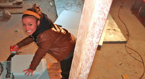 female student insulates a basement