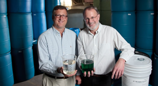 two men holding beakers of chemicals