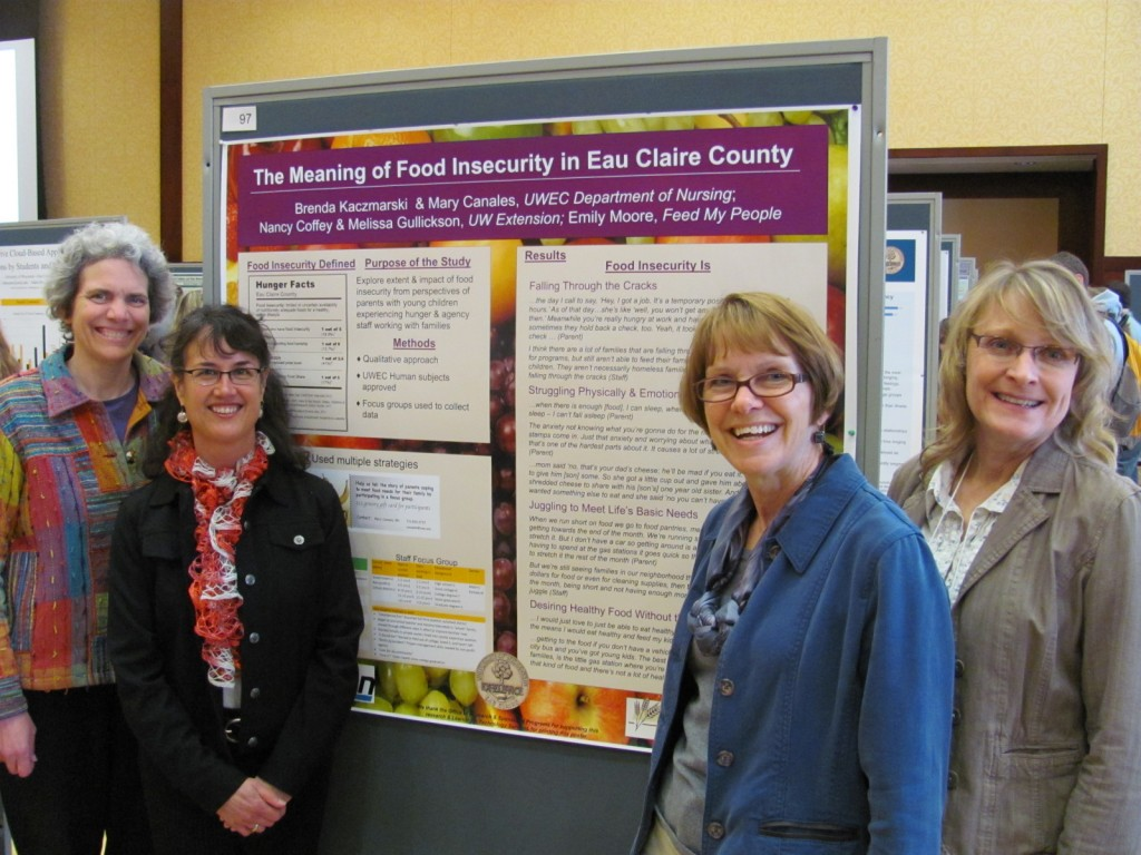 research team smiles in front of their poster presentation