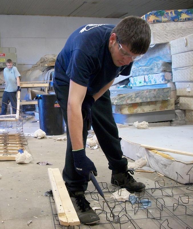 man dismantles a mattress