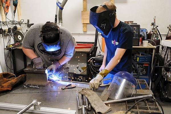 Chris Meyer shows a high school student how to use an arc welder