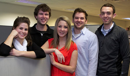 a group of Skyward Grads are seen smiling in their office