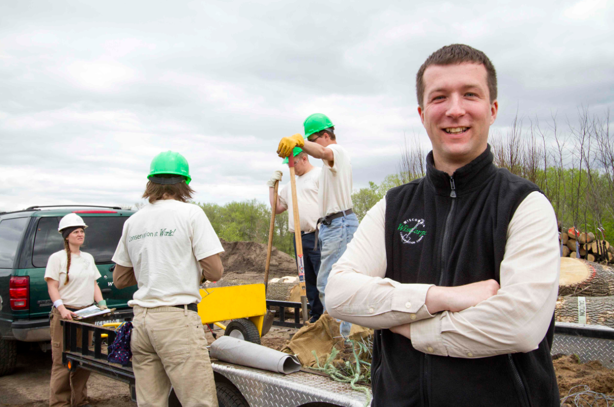 Brantner smiling with a crew working in the field