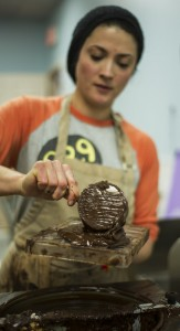 Mariana pours melted chocolate into a mold