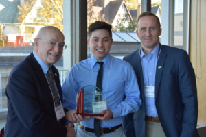 Luis Balleno receives his lkaward from Presdient Ray Cross and David Durian, Alliant