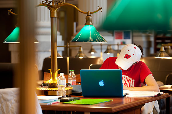 Picture of a student using a laptop at a desk in the Wisconsin Historical Society library reading room.
