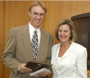 Greg Hutchins receives the 2002 teaching award on behalf of the UW-Extension 4-H Youth Development Program from Regent Elizabeth Burmaster.