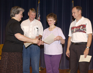 President Lyall recognizes (from left to right) Jim Albers, Nancy Westrum and Chuck McConnell for more than 30 years of service. (Jay Salvo photo)