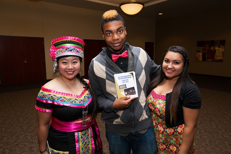 multicultural performance group including a woman in traditional Hmong dress, African American man and another non White woman