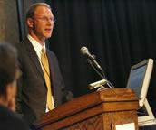 Cramer speaking at the podium