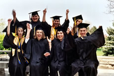 group of happy college graduates waving