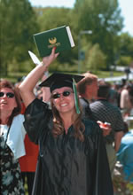 smiling college graduate holding up her  diploma