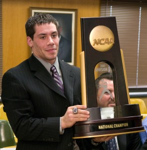 A UW-Whitewater football player displays the team's national championship trophy