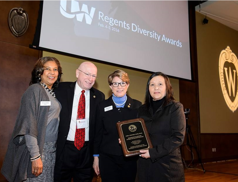 Chia Vang (right) receives award, pictured with (from left) Regent Eve Hall, President Ray Cross, and Regent President Regina Millner