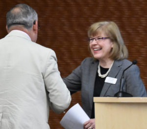 Photo of departing Executive Director and Corporate Secretary Jane Radue greeting Regent Jose Delgado